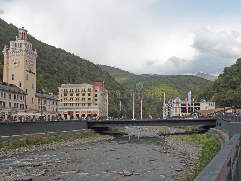 山区度假村在河,钟楼,桥梁,旅馆的堤防的罗莎Khutor 免版税库存照片