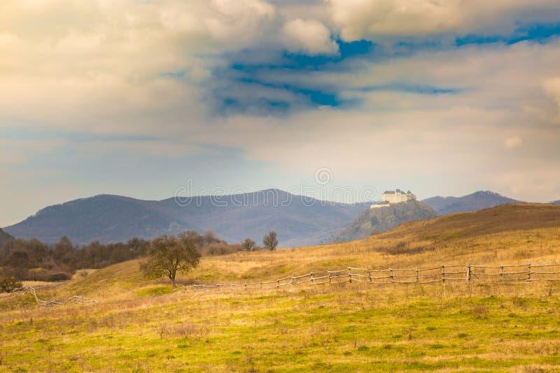 山和城堡剧烈的风景视图在背景中与多云天空和秋天树 库存图片