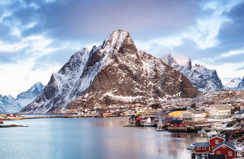 山和海在Lofoten海岛,挪威上咆哮 议院临近山 夜与山和镇的冬天风景的 免版税图库摄影