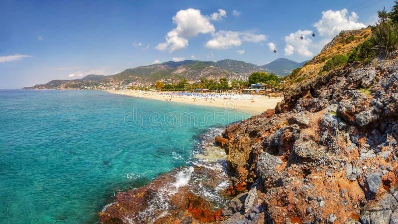 山和海景在晴朗的夏日在阿拉尼亚土耳其 在热带海滩和海岸线的美丽的景色通过土耳其岩石 库存图片