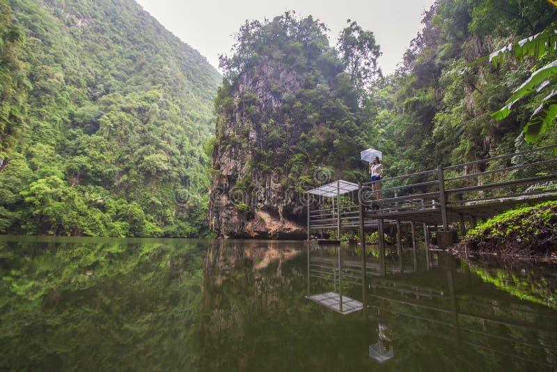 山和绿色密林围拢的平静的湖的美好的风景反射,作为支持observator的一名亚裔妇女 库存图片