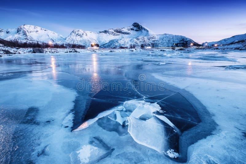 山土坎和冰冻结的湖表面上 在Lofoten海岛,挪威上的自然风景 免版税库存图片