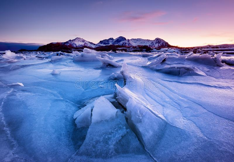 山土坎和反射冻结的湖表面上 在Lofoten海岛,挪威上的自然风景 免版税库存照片