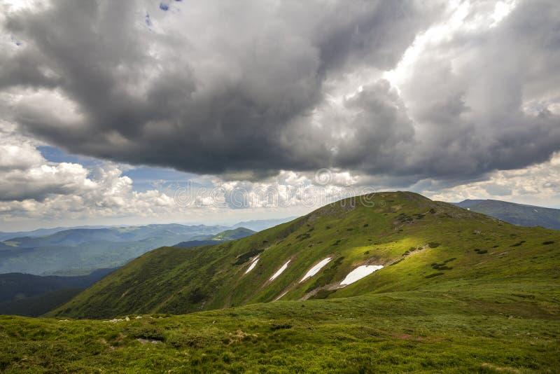 山土坎风景在剧烈的多云天空、夏天或者春天宽全景下 库存照片
