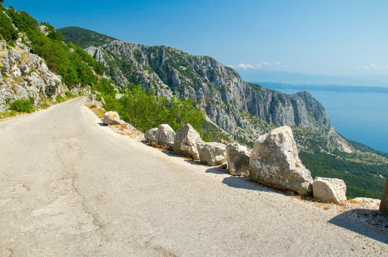 山在峰顶在Biokovo山脉和马卡尔斯卡前面里维埃拉小山和岩石的Sveti Jure上面的柏油路  库存图片