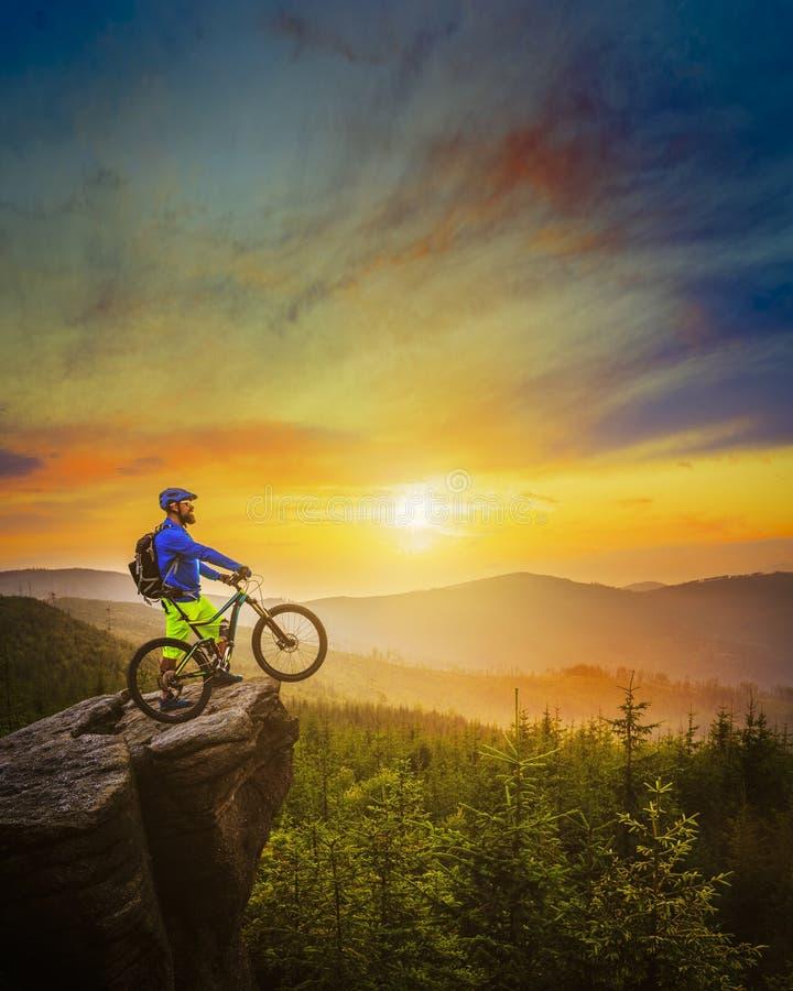 山在日落的骑自行车的人骑马在前面夏天的山的自行车 免版税图库摄影