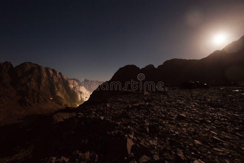 山在晚上,点燃与月光反对天空背景 库存图片