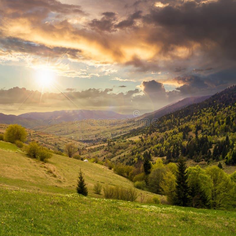 山坡草甸的村庄有山的森林的在日落 库存图片