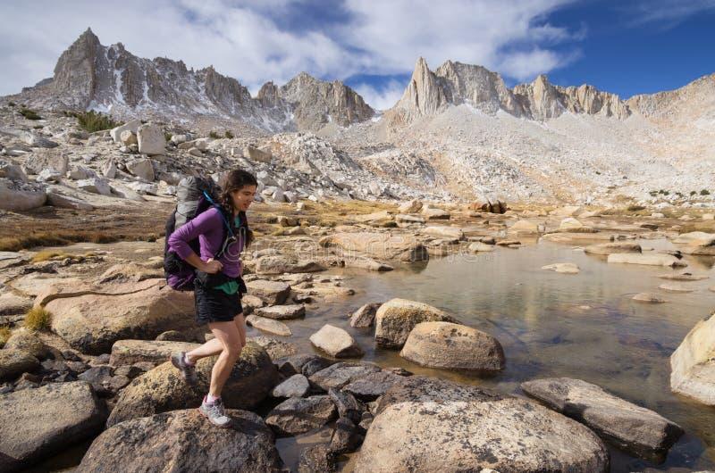 山妇女背包徒步旅行者 免版税库存图片