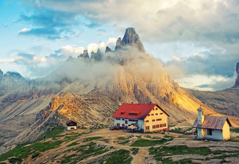 山小屋和教堂风景看法日落的在白云岩,意大利 免版税图库摄影