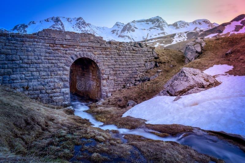 山小河瀑布风景和桥梁在日落,比利牛斯 免版税图库摄影