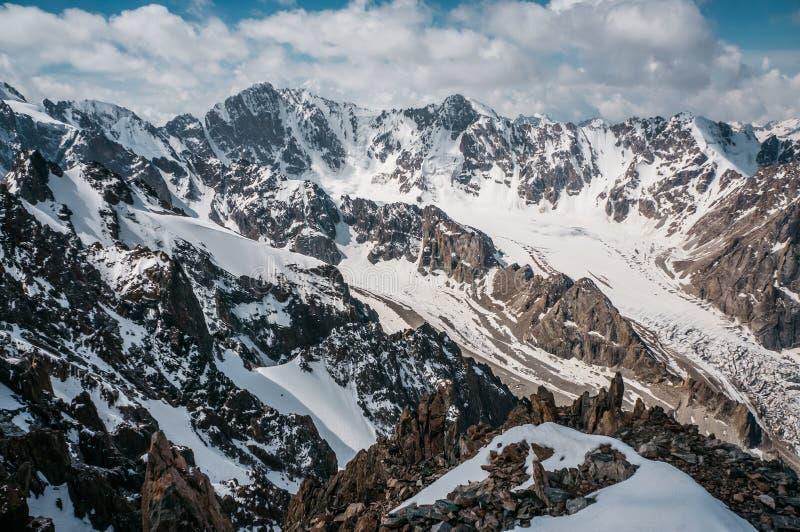 山岩石峰顶看法在雪在云彩下,丙氨酸Archa国民的 免版税库存照片