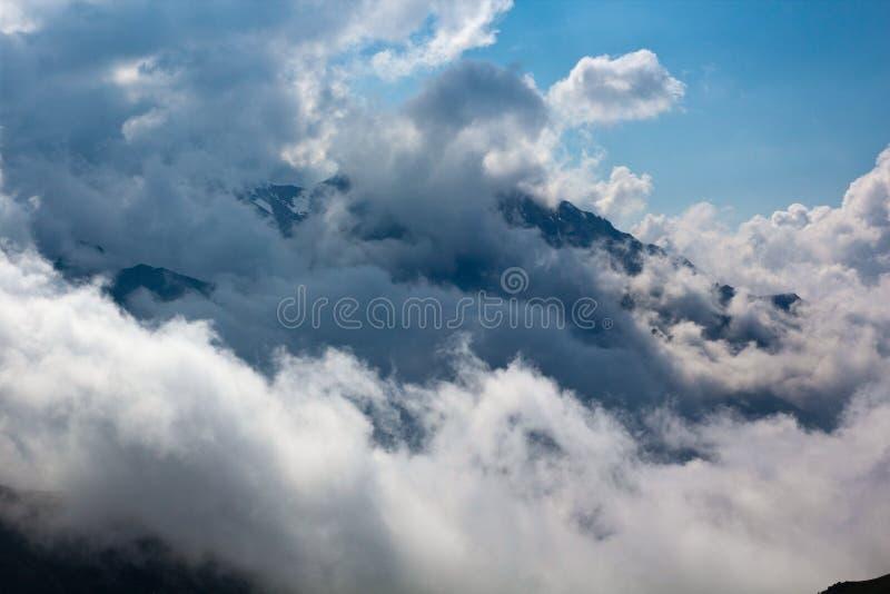 山峰在白色云彩大前面的环境里  免版税图库摄影