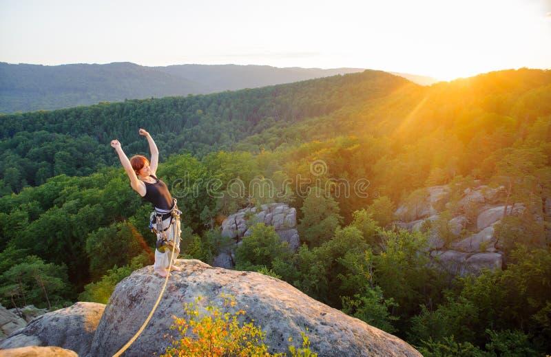 山峰的女孩登山人在高处在晚上 免版税库存照片