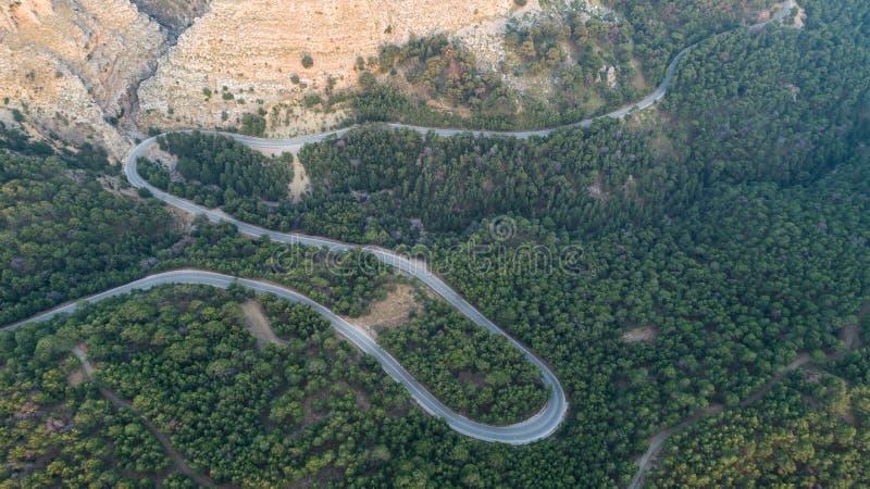 山曲线路鸟瞰图  日落的绿色森林在夏天在欧洲 与柏油路,在岩石的树的风景 库存照片