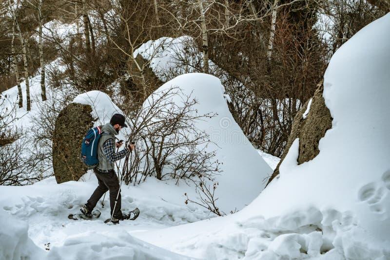 山步行的徒步旅行者在雪靴 单独一个人在森林下降山 冬天山旅游业 免版税库存图片