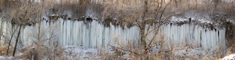 山沟的倾斜的全景,水streamlets在霜跑并且结冰,形成冰柱冰冷的墙壁关于 库存照片