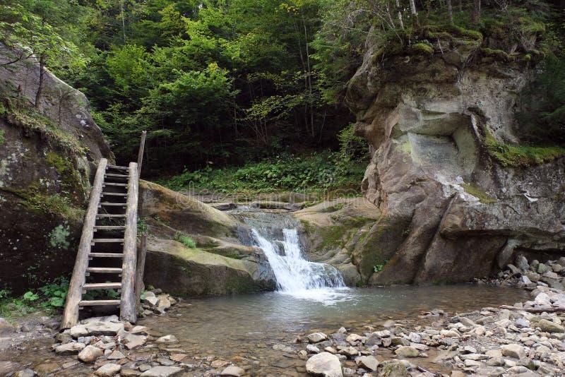 山河是与瀑布和岩石 免版税库存图片