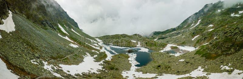 山湖和雪全景围拢它的 库存图片