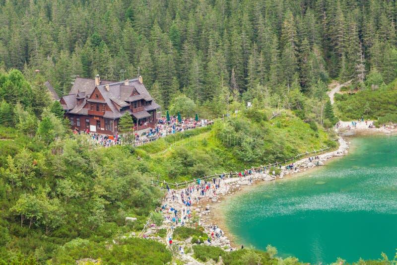 山瑞士山中的牧人小屋的游人 免版税库存图片