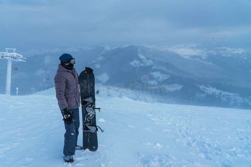 山的一个人 雪板在手中 体育运动 挡雪板 免版税库存照片