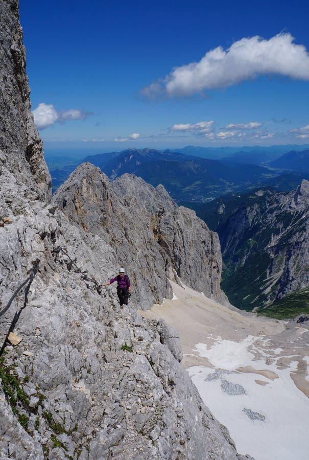 山的一个岩石表面的登山家妇女 图库摄影