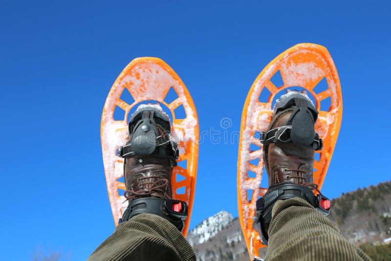 山的人与橙色雪靴 免版税图库摄影