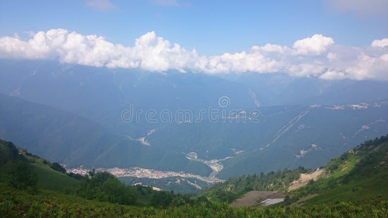 山的全景和与低云的Aibga土坎 雪和新鲜的绿草遗骸在山在附近 免版税库存图片