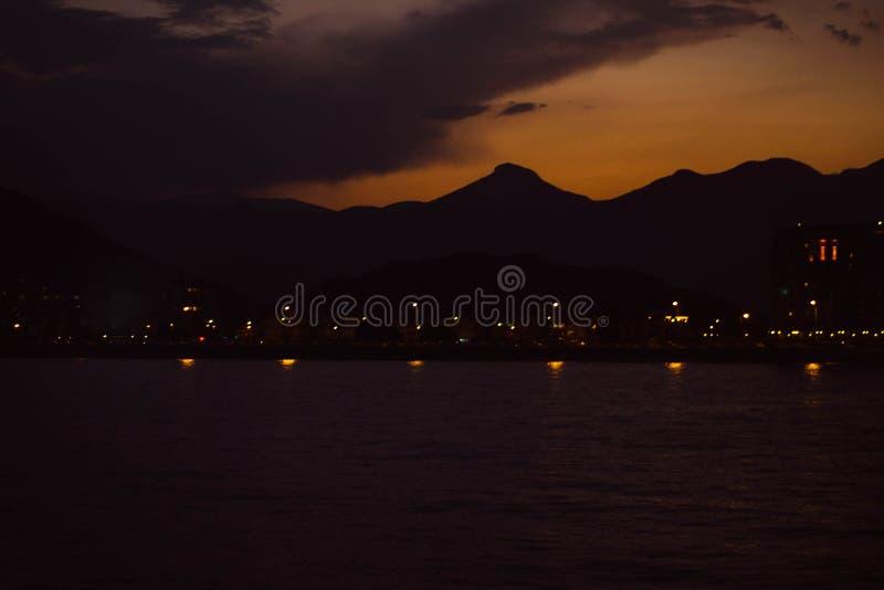 山的剪影的看法在土耳其的海岸的在晚上 与光的风景在黑暗的沿海 库存图片