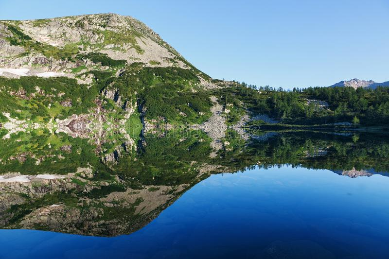 山的反射在水的,山镜象在水中 库存图片
