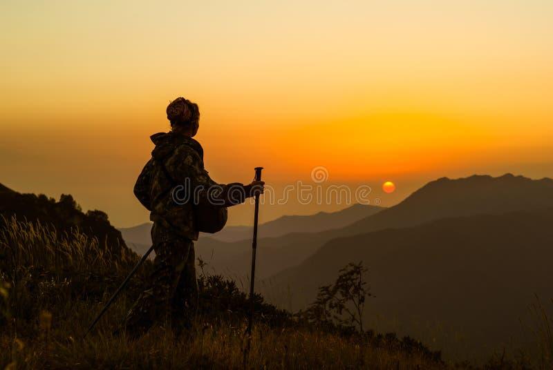 山的女孩旅客在日落 免版税图库摄影