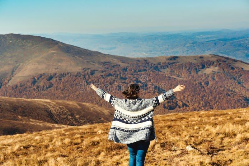 山的愉快的自由女孩 在秋天山顶部的妇女上升的手 旅行、自由和幸福,成就 图库摄影