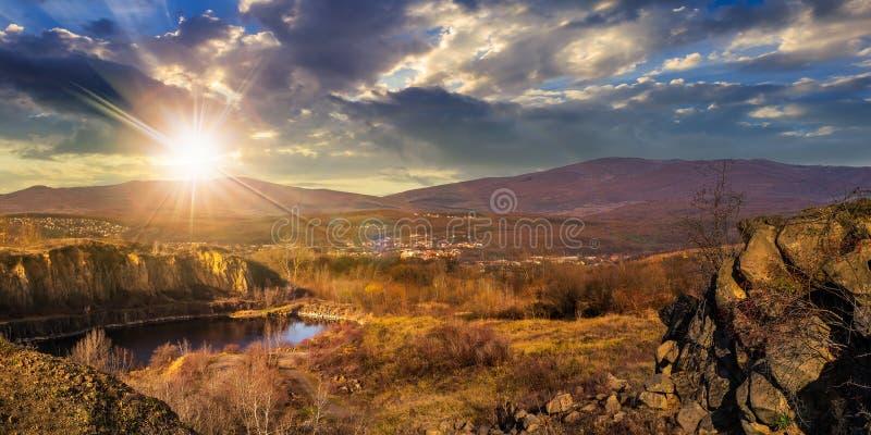 山的湖挖掘靠近城市在日落 免版税库存图片