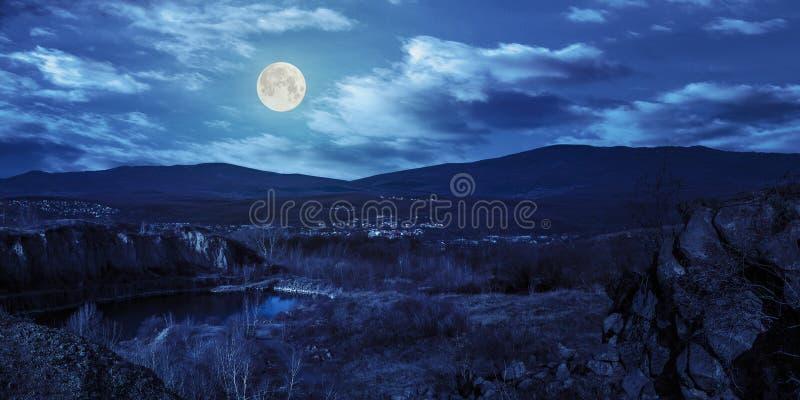 山的湖挖掘靠近城市在晚上 免版税库存图片