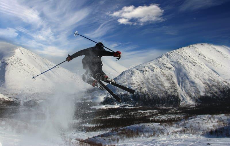 山的滑雪者在飞行中从返回 库存照片