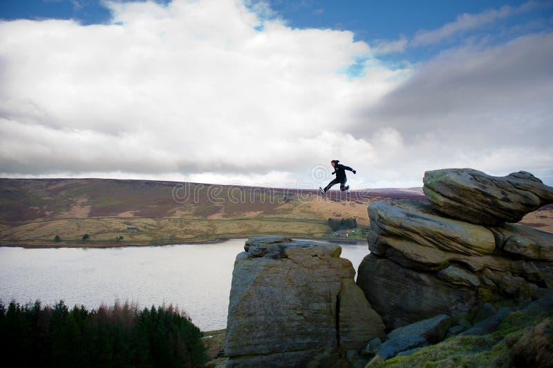 山的跳跃的人 免版税库存照片