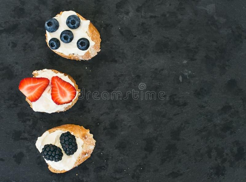 山羊乳干酪和莓果迷你sandwitches在一黑暗的石backgro 库存照片