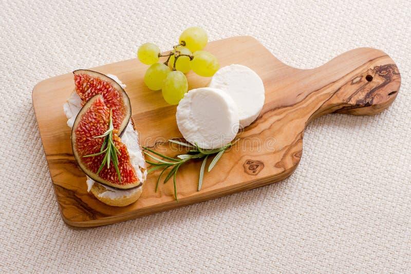 山羊乳干酪用成熟无花果和葡萄 免版税库存照片