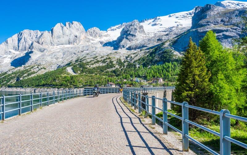 山路的, Passo Fedaia Fedaia通行证摩托车骑士,在马尔莫拉达山断层块和近的湖Fedaia的脚,白云岩, F 免版税图库摄影