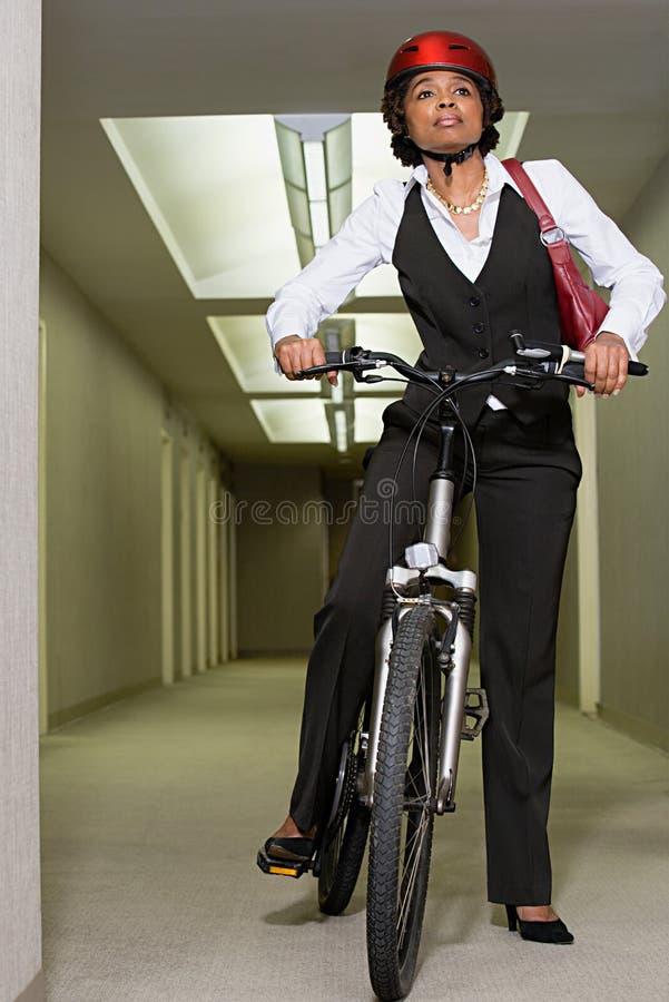 登山车的女性办公室工作者 库存照片
