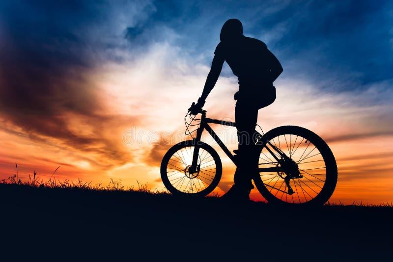登山车的运动人反对五颜六色的天空 图库摄影