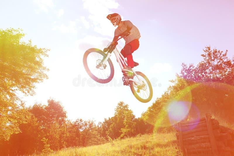 登山车的运动员在从跳板的一个跃迁飞行 库存照片
