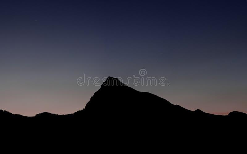 山风景剪影在日落以后的晚上天空下 免版税库存照片