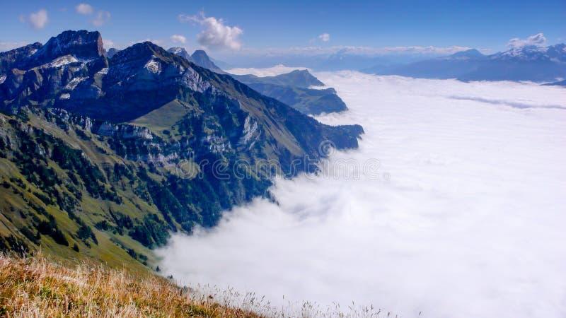 山风景在与下面厚实的云层的一个美好的夏日在谷  免版税库存图片