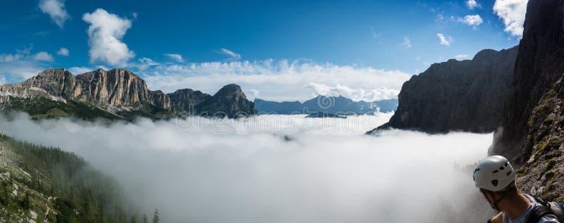 山风景在与锋利的峰顶的秋天和云堤和享受看法的攀岩运动员 库存图片