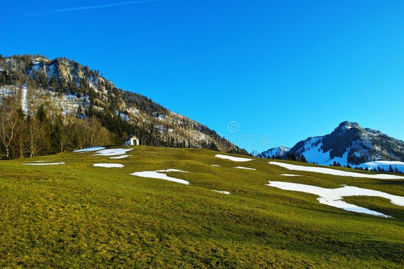 山风景的山坡教堂在春天 免版税库存照片