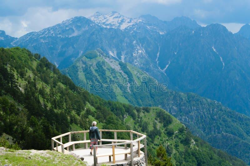 山风景,一个木大阳台的妇女,敬佩阿尔巴尼亚阿尔卑斯美丽的景色  免版税库存图片