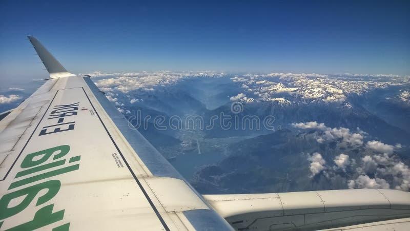 从山飞机窗口的看法与雪的在上面、云彩、翼和蓝天 免版税库存照片