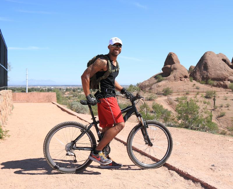 山骑自行车的人: 为沙漠山准备 库存图片