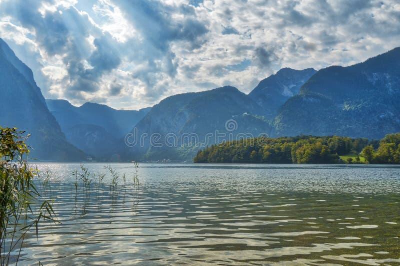 山HDR美好的风景视图与剧烈的多云天空的在Hallstatt村庄附近的一个湖上在奥地利 免版税库存照片